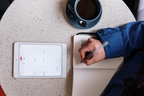 A person writing on a journal, looking at a calendar on an iPad